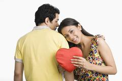 Woman leaning on a man's shoulder and holding a present - stock photo