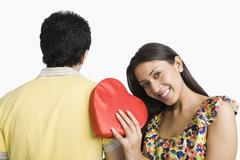 Woman leaning on a man's shoulder and holding a present Stock Photos