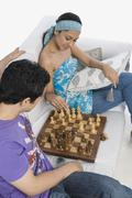 High angle view of a couple playing chess - stock photo