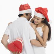 Man hiding a Christmas present to surprise his girlfriend - stock photo