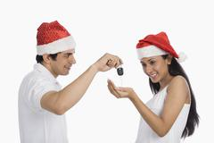 Man giving car key as a Christmas present to his girlfriend - stock photo