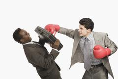 Businessman defending himself from the punch of his colleague Stock Photos