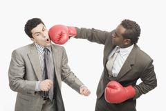Businessman punching his co-worker with boxing gloves - stock photo