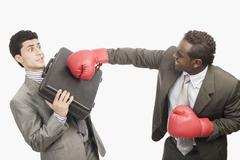 Businessman defending himself from the punch of his colleague - stock photo