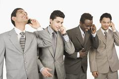 Four businessmen talking on mobile phones Stock Photos