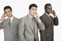 Three businessmen talking on mobile phones - stock photo