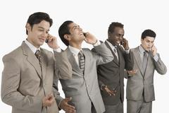 Four businessmen talking on mobile phones - stock photo