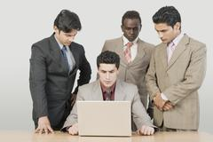 Three businessmen looking at their colleague using a laptop - stock photo
