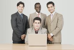Portrait of four businessmen in front of a laptop - stock photo