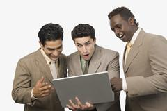 Three businessmen standing with a laptop - stock photo