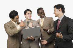 Stock Photo of Four businessmen smiling in front of a laptop