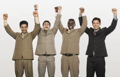 Stock Photo of Portrait of four businessmen with arms raised