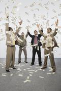 Banknotes falling over four businessmen Stock Photos