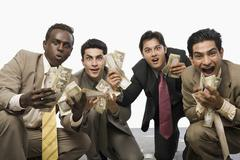 Portrait of four businessmen crouching and holding currency notes - stock photo