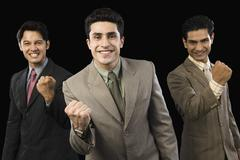 Portrait of three businessmen clenching fists Stock Photos