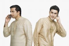 Two men talking on mobile phones - stock photo