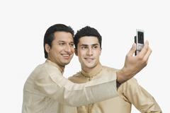 Two men taking a picture of themselves with a mobile phone - stock photo
