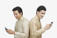Two men text messaging on mobile phones - stock photo