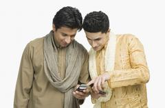 Two men text messaging on mobile phones Stock Photos