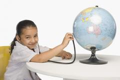 Girl examining a globe with a stethoscope Stock Photos