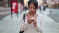 Asian woman in city walking talking texting cellphone smart phone Stock Footage