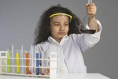Girl dressed as scientist researching in the laboratory - stock photo
