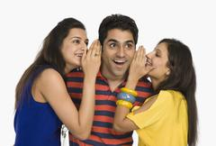 Two women whispering to a man Stock Photos