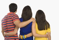Rear view of three friends standing - stock photo