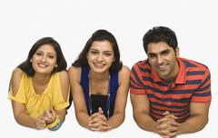 Portrait of three friends lying side by side and smiling Stock Photos