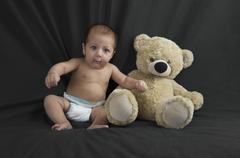 Baby boy sitting with a teddy bear Stock Photos