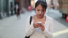 Asian woman walking talking texting cellphone smart phone Stock Footage