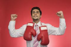 Businessman with boxing gloves clenching his fists Stock Photos