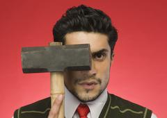 Portrait of a businessman holding a sledgehammer in front of his face - stock photo