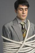Stock Photo of Close-up of a businessman tied up with ropes