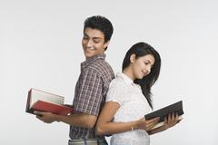 College students standing back to back and reading books - stock photo