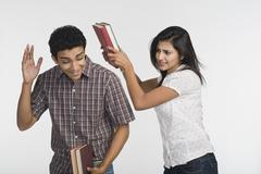 Stock Photo of Woman beating her friend with a book