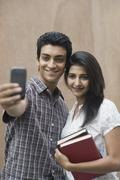 College students taking a picture of themselves with a camera mobile - stock photo