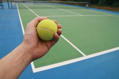 Tennis ball on player hand Stock Photos