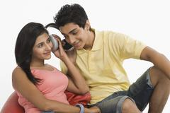Couple listening to headphones - stock photo