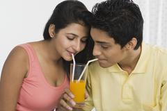 Couple sharing juice from a glass Stock Photos