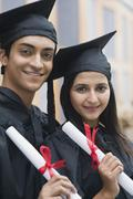 Couple in graduation gowns holding diplomas and smiling - stock photo