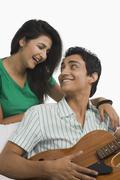 Man playing a guitar beside a woman - stock photo