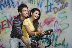 Stock Photo of Couple riding a bicycle and smiling