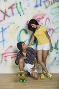 Couple with a skateboard in front of a graffiti covered wall - stock photo
