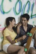 Couple sitting with a skateboard in front of a graffiti covered wall - stock photo