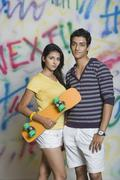 Portrait of a couple standing with a skateboard in front of a graffiti covered - stock photo