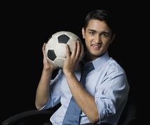 Businessman holding a soccer ball Stock Photos