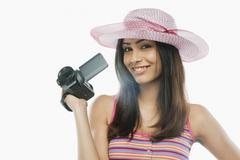 Portrait of a woman filming with a home video camera - stock photo