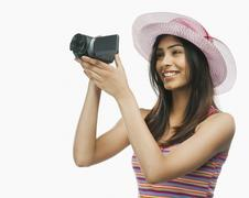Close-up of a woman filming with a home video camera - stock photo