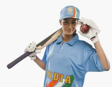 Portrait of a female cricketer holding a cricket bat and a ball Stock Photos